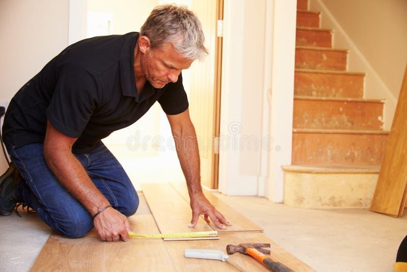 Équipez étendre le plancher en bois de panneau pendant une rénovation de maison photos libres de droits