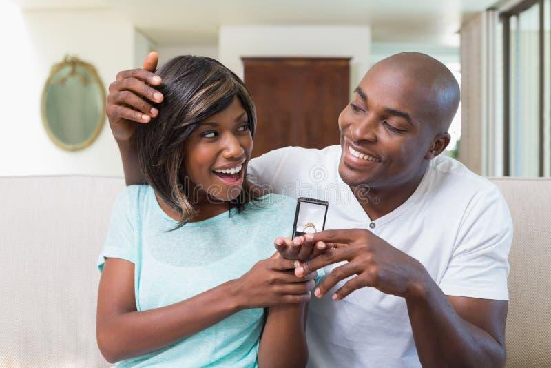 Équipez étonnant son amie avec une bague de fiançailles sur le divan image stock