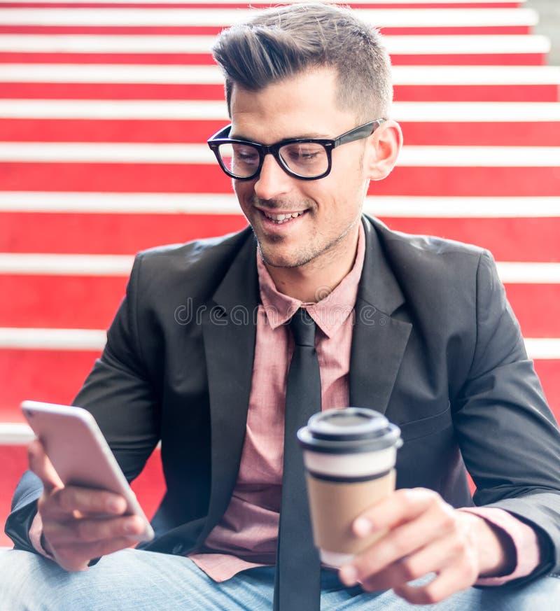 Équipez étroit avec un téléphone portable et un café photo libre de droits