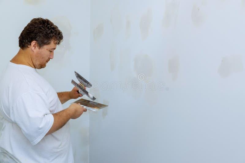 Équipez aligner un mur avec la spatule fonctionnant avec le mur de mastic et de spatule photo stock