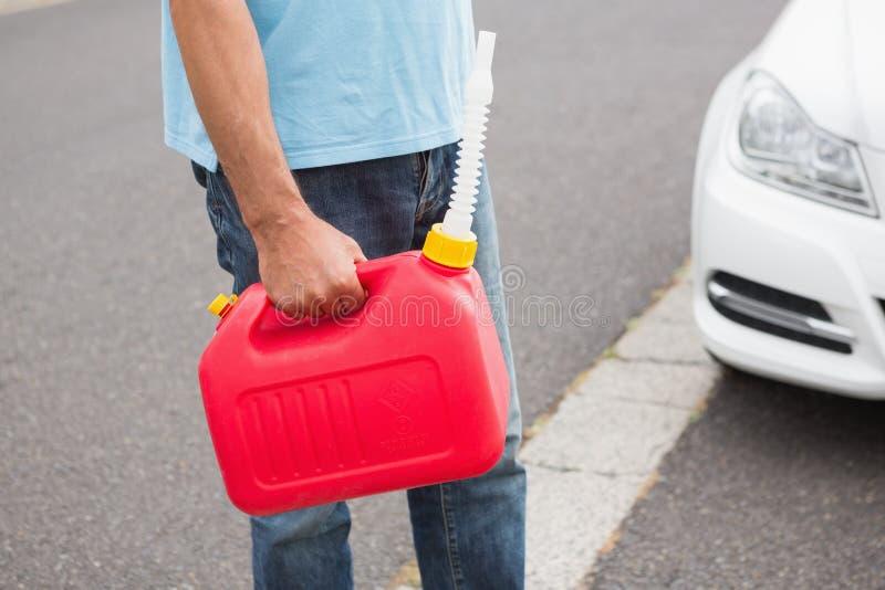 Équipez apporter la boîte métallique d'essence à une voiture décomposée image libre de droits