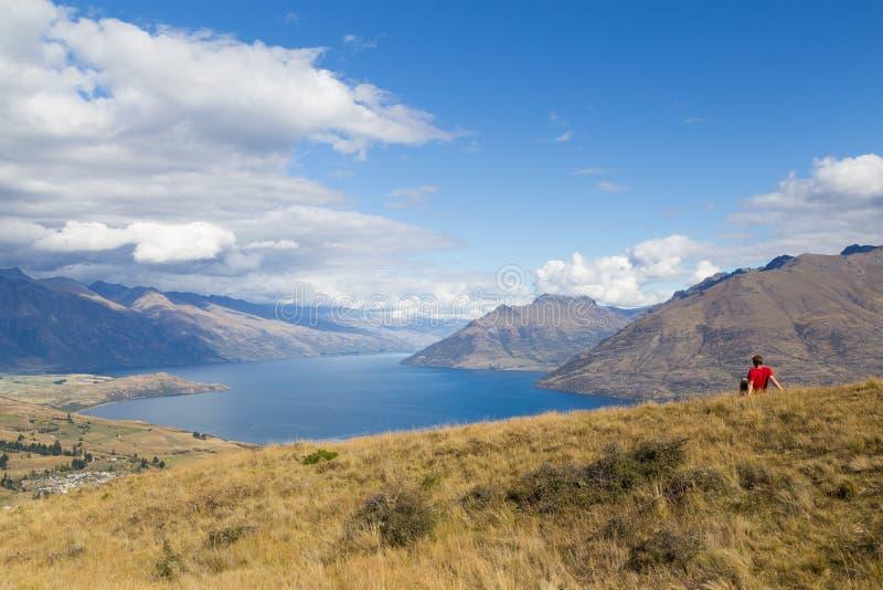 Équipez apprécier la vue de la colline de Queenstown, Nouvelle-Zélande image stock