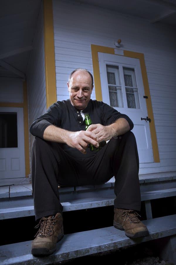 Équipez apprécier une bière sur son porche avant photos stock