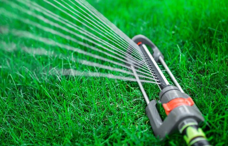 Équipez arroser le jardin, fermez-vous d'arroseuses vers le haut de la photo photos stock