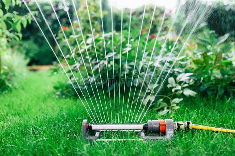 Équipez arroser le jardin, fermez-vous d'arroseuses vers le haut de la photo images stock