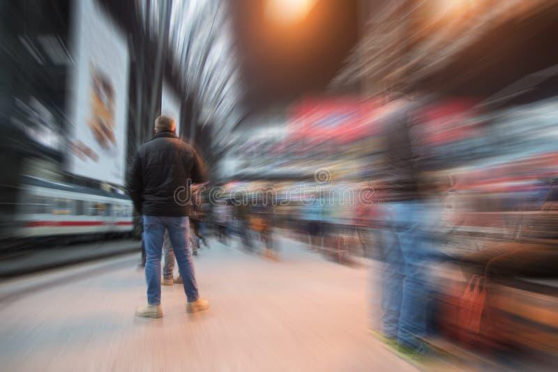 Équipez attendre le train sur une plate-forme dans le grand chemin de fer de ville images libres de droits