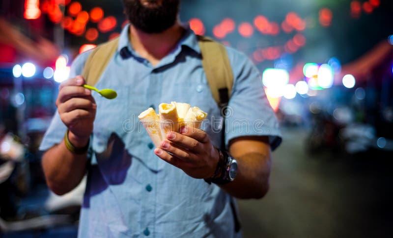 Équipez avoir des petits pains de crème glacée sur le marché de nuit photo libre de droits