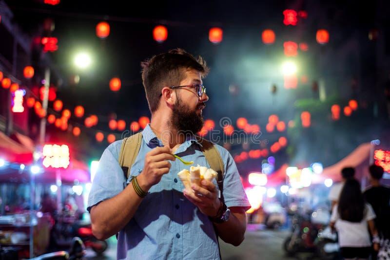 Équipez avoir des petits pains de crème glacée sur le marché de nuit photos libres de droits