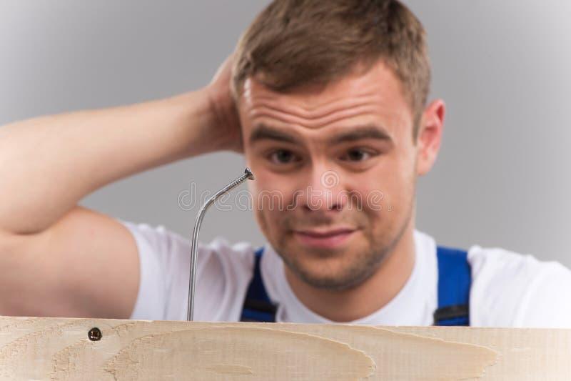 Équipez avoir la difficulté obtenant le clou martelé dans le bois images libres de droits