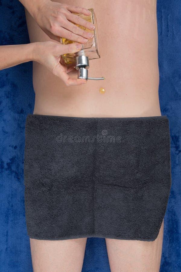 Équipez avoir le traitement de station thermale d'Ayurveda d'huile sur le sien de retour image stock