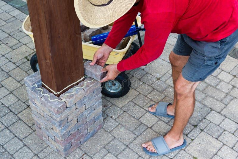 Équipez coller les briques grises autour d'une jambe en bois de belvédère photographie stock
