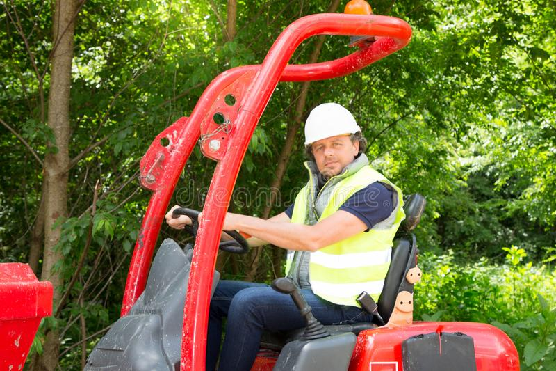 Équipez conduire l'excavatrice Backhoe avec le chapeau blanc de sécurité images stock