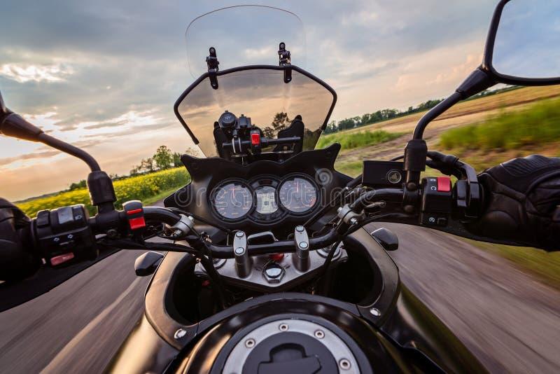Équipez conduire sa moto sur la route de campagne d'asphalte photo stock