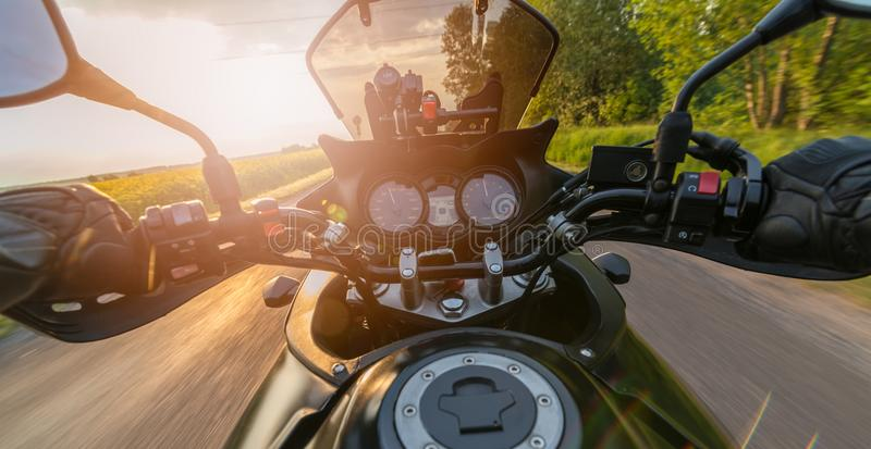 Équipez conduire sa moto sur la route de campagne d'asphalte photos libres de droits