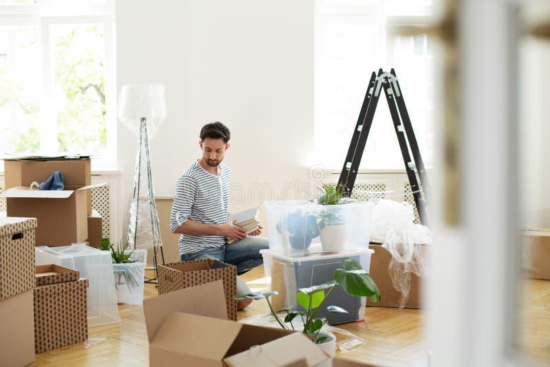 Équipez déballer la substance des boîtes de carton après la relocalisation à la nouvelle maison image stock