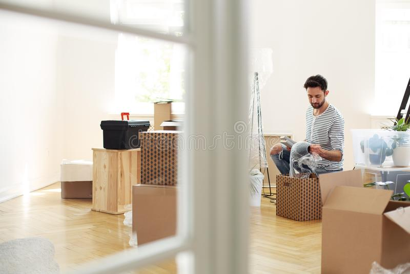 Équipez déballer la substance des boîtes tout en fournissant le nouvel appartement après r photographie stock