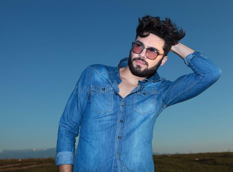 Équipez dans la chemise de blues-jean posant contre le ciel bleu photographie stock libre de droits
