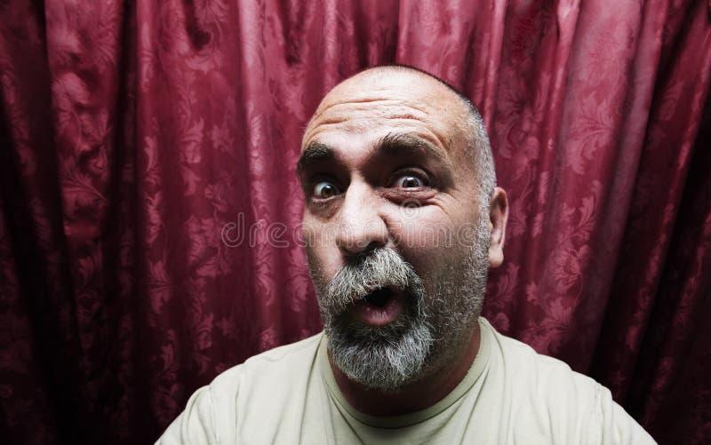 Équipez effectuer un visage drôle devant les rideaux rouges photos libres de droits