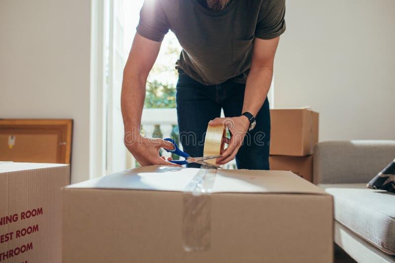 Équipez emballer sa substance de ménage dans des caisses d'emballage et le cachetage  image libre de droits
