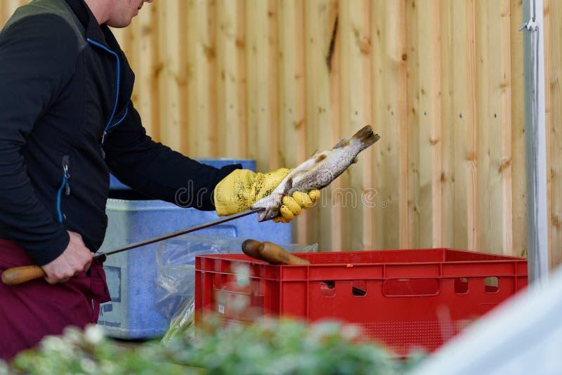 Équipez empaler un poisson pour le préparer pour le barbecue photo libre de droits