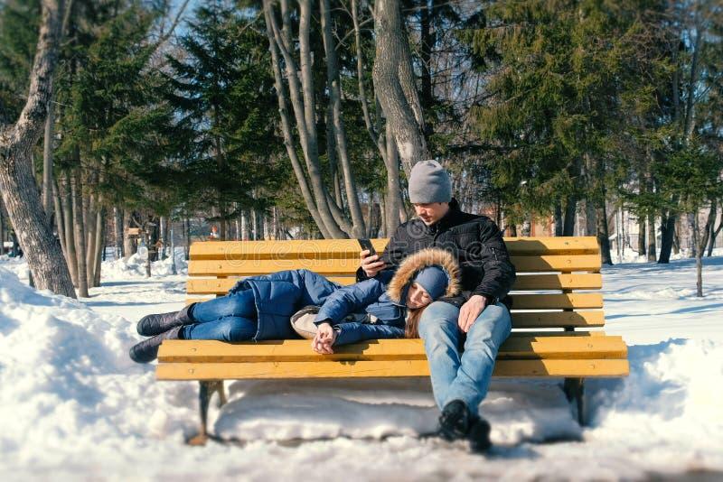 Équipez et un repos de femme ensemble sur un banc en parc de ville d'hiver photographie stock libre de droits