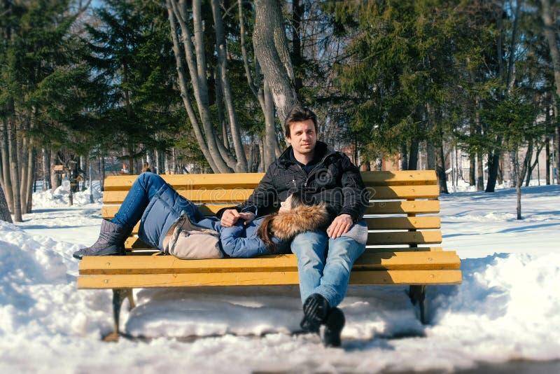 Équipez et un repos de femme ensemble sur un banc en parc de ville d'hiver Jour d'hiver ensoleillé image libre de droits