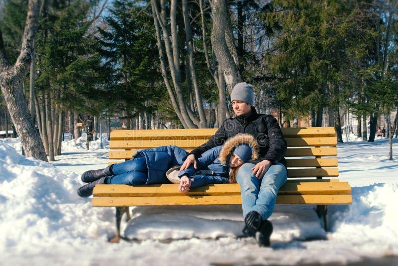 Équipez et un repos de femme ensemble sur un banc en parc de ville d'hiver Jour d'hiver ensoleillé images libres de droits