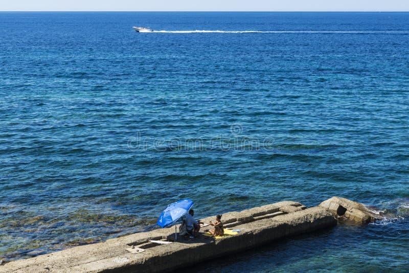 Équipez et une femme s'asseyant sur un mur en pierre sur la mer images libres de droits