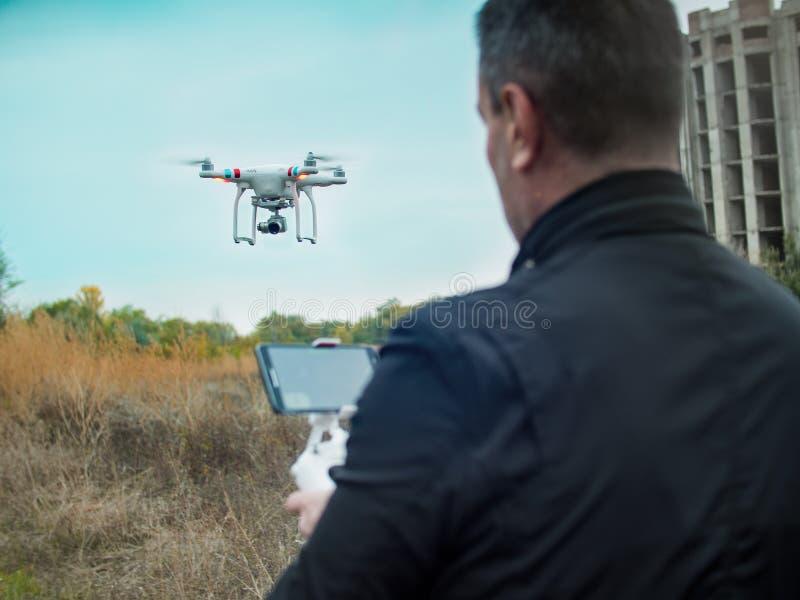 Équipez exploiter un hélicoptère de quadruple de bourdon avec l'appareil photo numérique à bord photos libres de droits