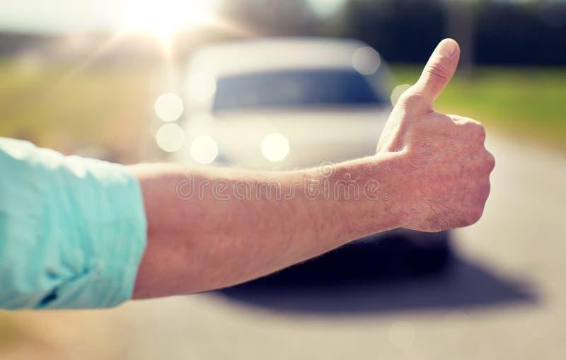 Équipez faire de l'auto-stop et arrêter la voiture avec des pouces  images stock