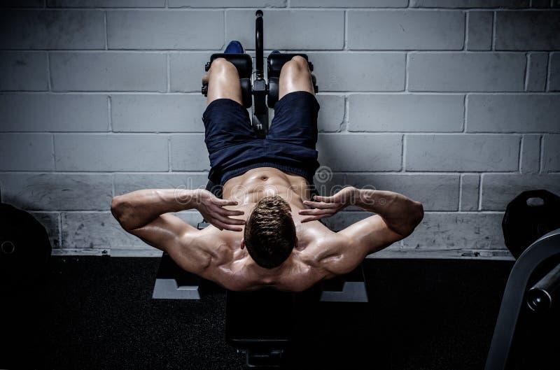Équipez faire des exercices pour abdominal dans le studio du gymnase photo stock