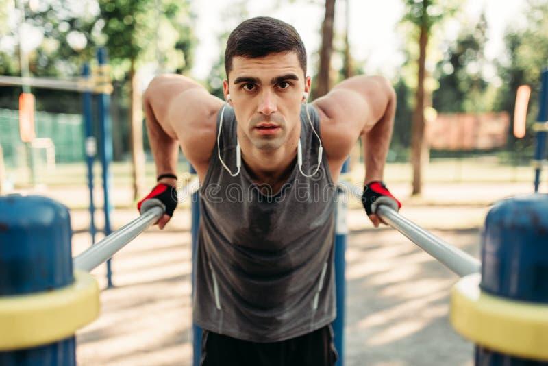 Équipez faire l'exercice sur des barres parallèles, vue de face photographie stock