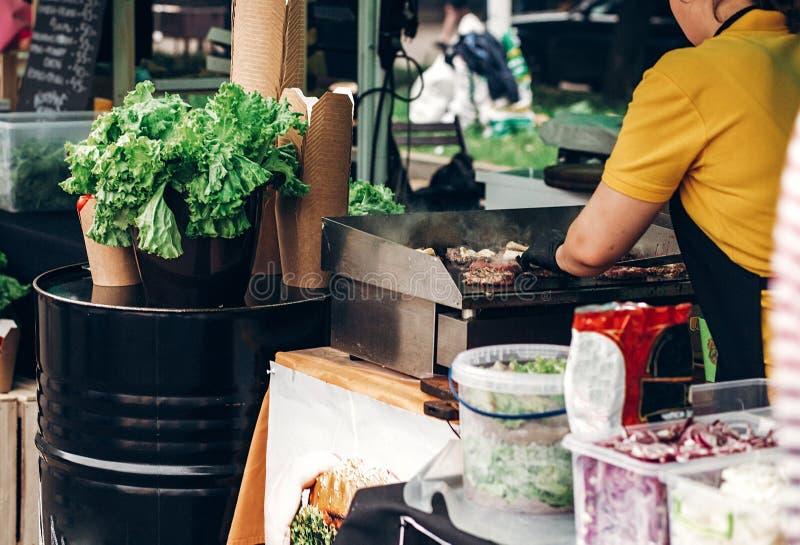 équipez faire les hamburgers, la viande de torréfaction et les légumes sur le gril chef photographie stock