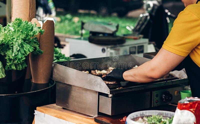 équipez faire les hamburgers, la viande de torréfaction et les légumes sur le gril chef photos libres de droits