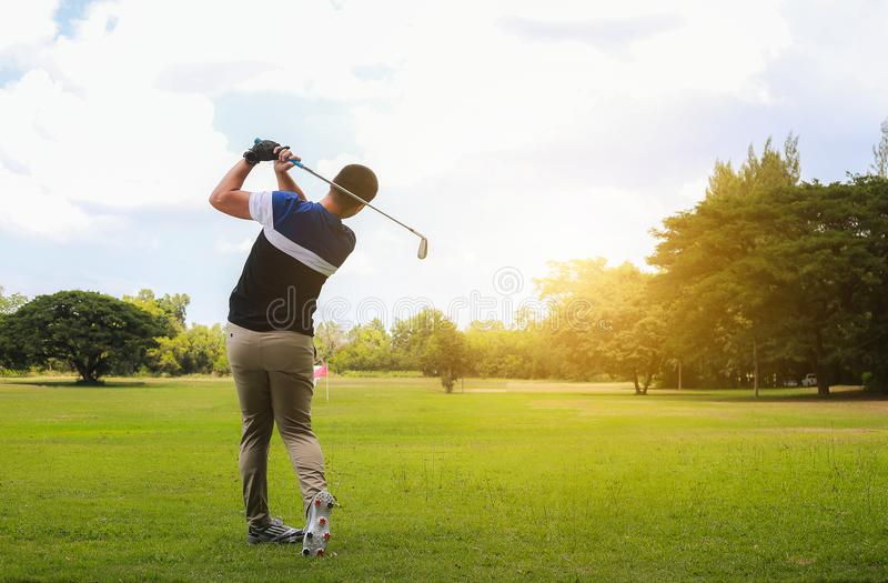 Équipez frapper le tir de golf avec le club sur le cours tandis qu'été au su image libre de droits