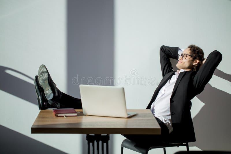 Équipez garder des jambes sur la table et travailler sur l'ordinateur portable dans le bureau photo stock