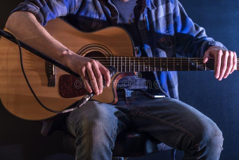 équipez jouer la guitare acoustique sur un fond noir, le concept de musique, bel éclairage sur l'étape photo stock