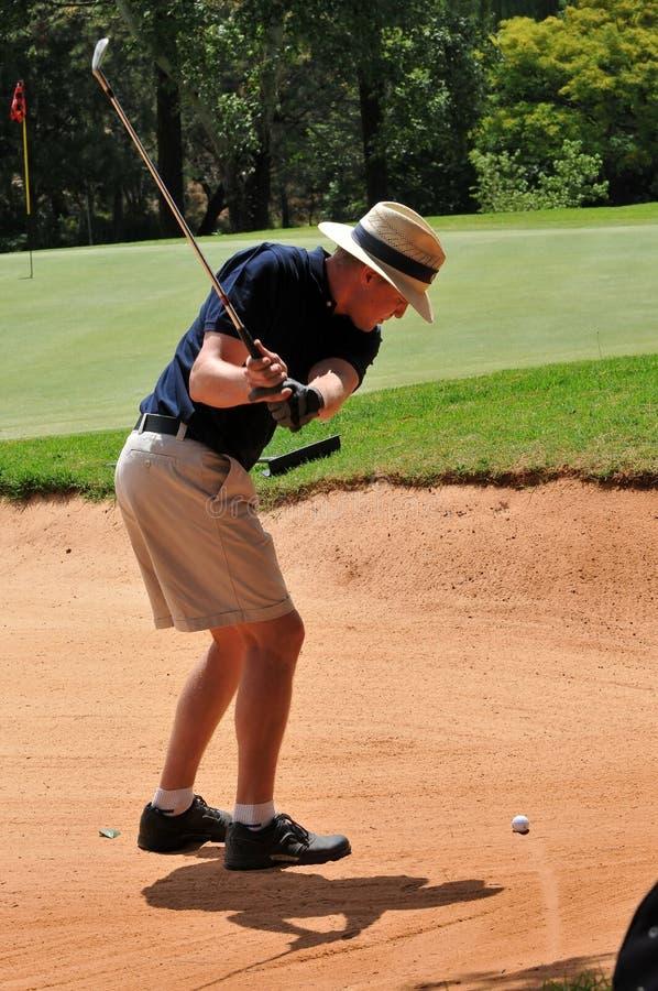 Équipez jouer le projectile de golf hors de la soute de sable sur le vert photographie stock libre de droits
