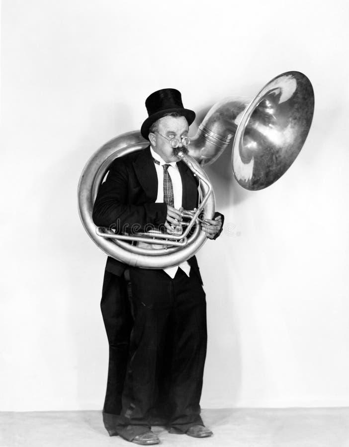 Équipez jouer un tuba dans un chapeau supérieur (toutes les personnes représentées ne sont pas plus long vivantes et aucun domain photographie stock