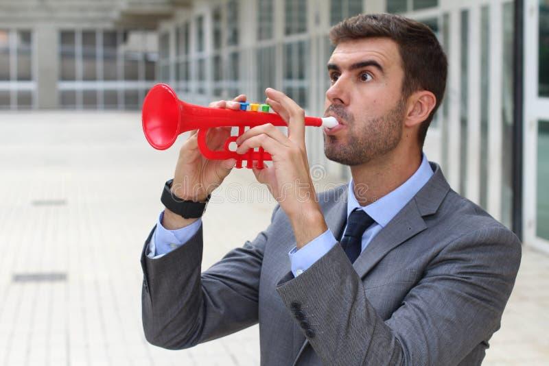 Équipez jouer une trompette en plastique dans le bureau image libre de droits