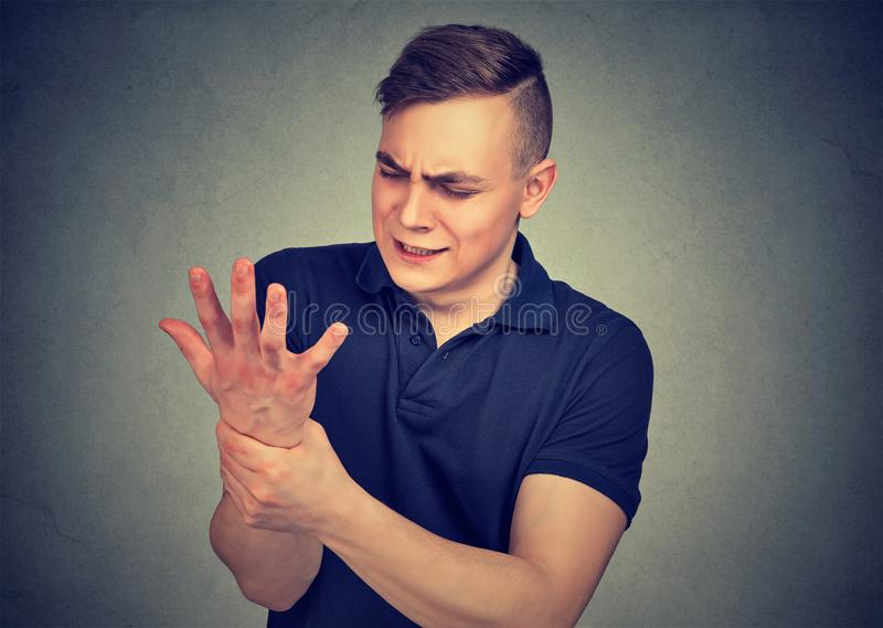 Équipez juger son poignet douloureux d'isolement sur le fond gris de mur Douleur d'entorse photographie stock libre de droits