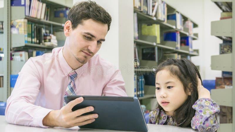 Équipez l'étudiant de professeur et d'enfant apprenant et regardant sur le comprimé devic photos stock
