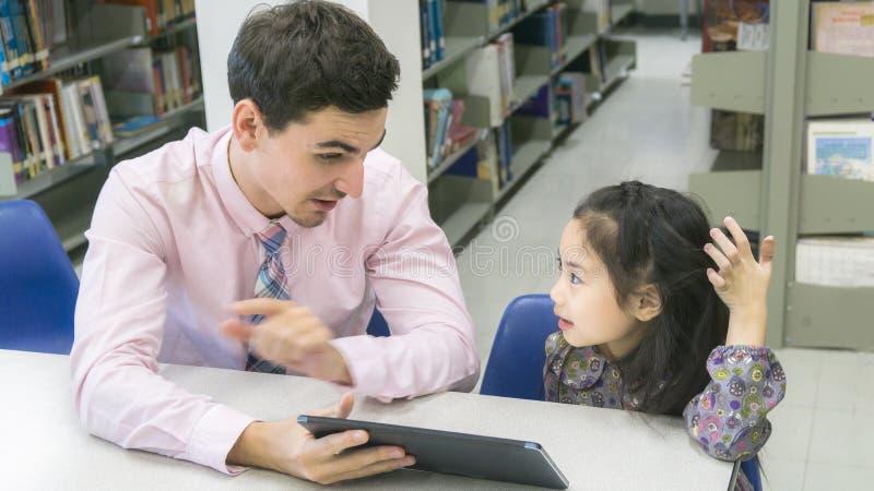 Équipez l'étudiant de professeur et d'enfant apprenant et regardant sur le comprimé devic photo stock