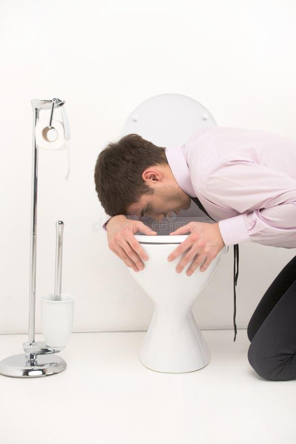 Équipez l'agenouillement vers le bas dans la salle de bains, vomissant dans la toilette images libres de droits
