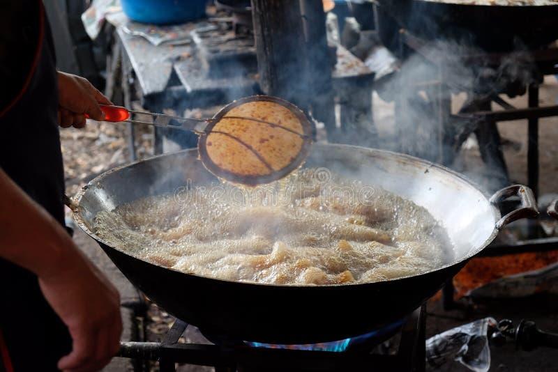Équipez l'aile de poulet frit en bouillant l'huile chaude photographie stock libre de droits