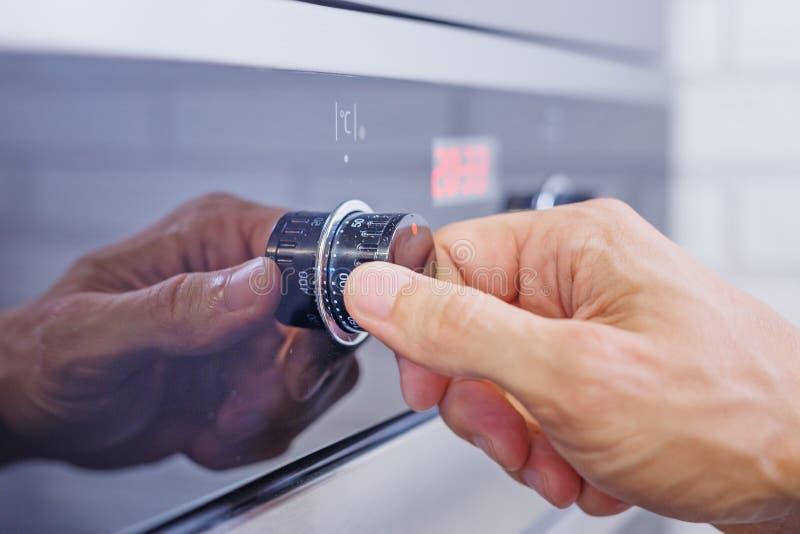 Équipez l'arrangement de main faisant cuire le mode sur le four électrique Le bouton-poussoir masculin de doigt sur le panneau de photographie stock libre de droits