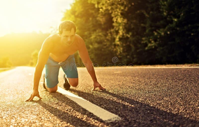 Équipez l'athlète courant sur la nature au coucher du soleil photos libres de droits