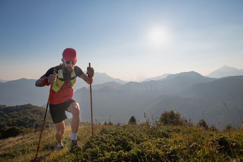 Équipez l'athlète de la ciel-incursion dans les montagnes avec des bâtons de poteaux vers le haut photographie stock libre de droits