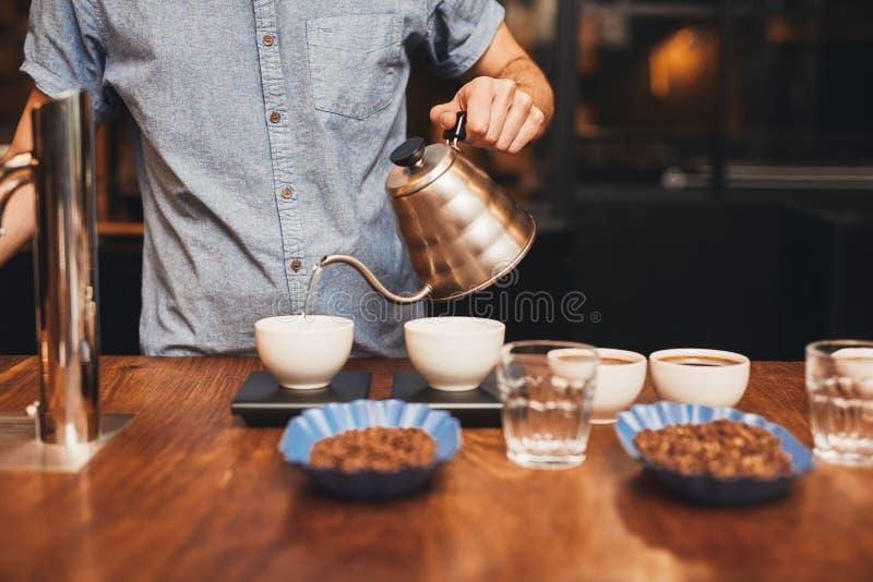 Équipez l'eau de versement dans la tasse de café sur une échelle numérique photo libre de droits