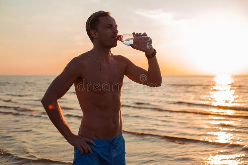 Équipez l'eau potable après sa séance d'entraînement sur la plage images stock